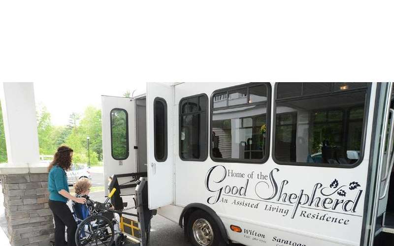 a woman in a wheelchair being lifted into the back end of a bus