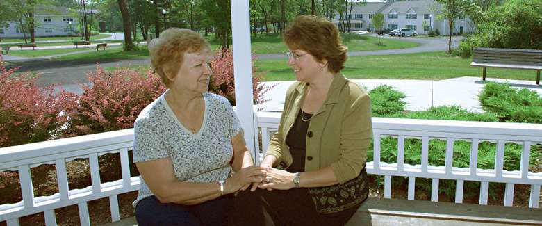 one woman sitting next to another woman on an outdoor deck