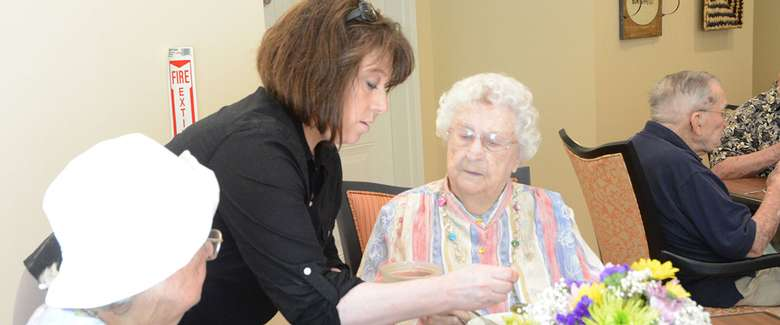 woman in a black shirt helping with an elderly woman's food on the table
