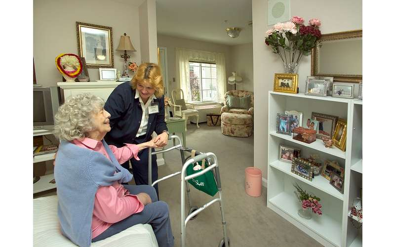 a woman with an elderly woman in a bedroom