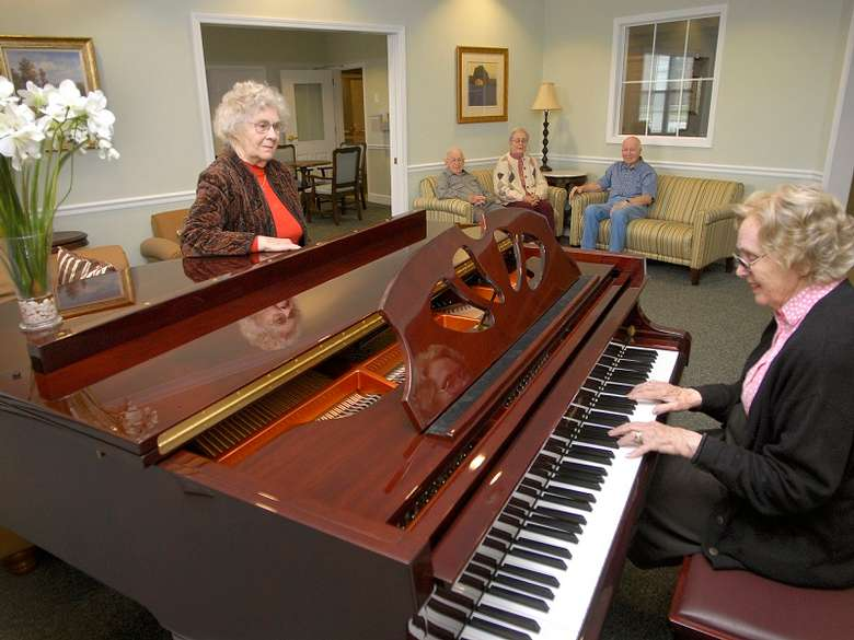 an elderly woman playing the piano while another woman watches