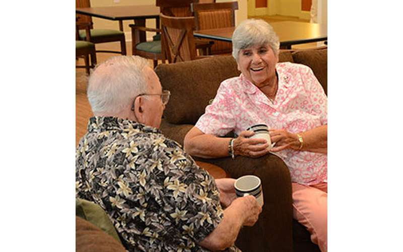 an elderly man and woman smiling over coffee