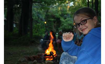 a girl sitting at a campfire