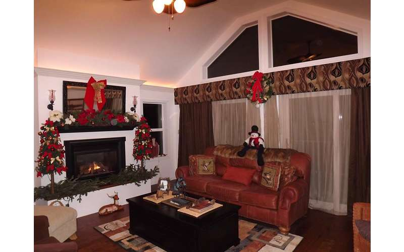 a living room that is decorated for the holidays, there is a red couch and a fireplace in it