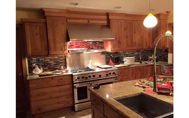 a kitchen with wooden cabinets, lights on the ceiling, and an oven