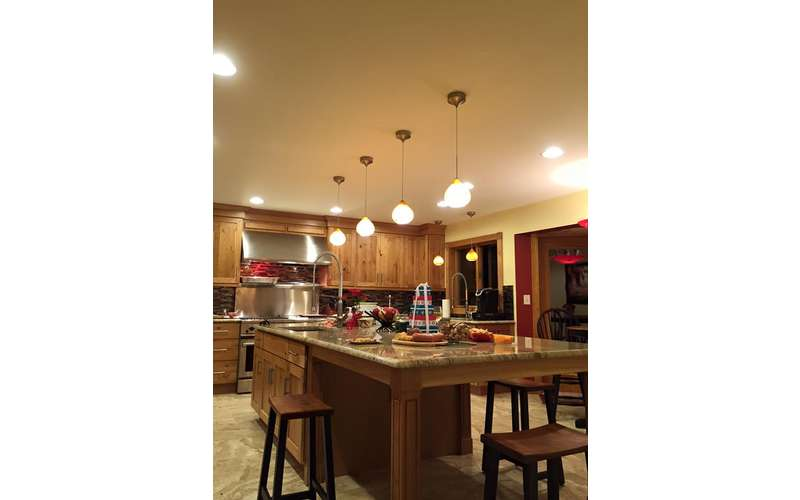 a kitchen with a line of lights hanging from the ceiling, an island in the center, and cabinets along the back side