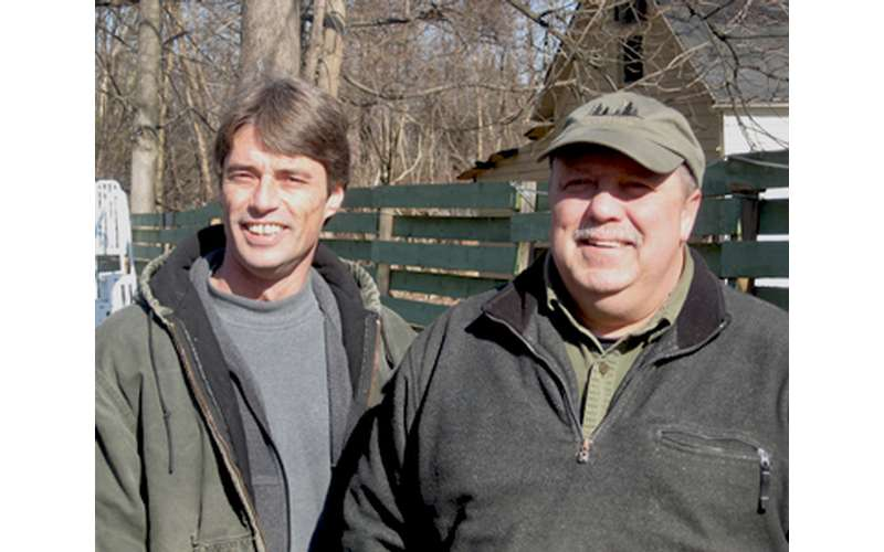two men standing outside near a fence