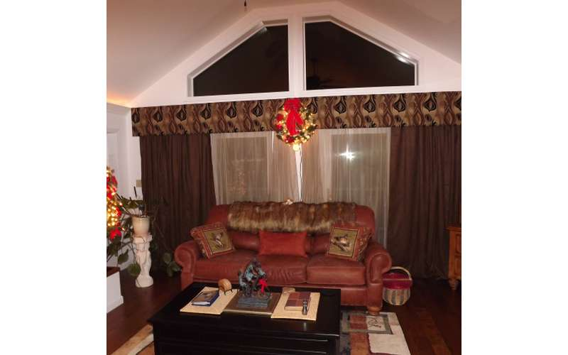 a wreath hanging above a red couch in a living room