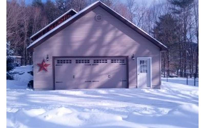 during winter with snow on the ground, there is a garage with a large front door