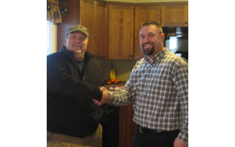 two men shaking hands inside a kitchen
