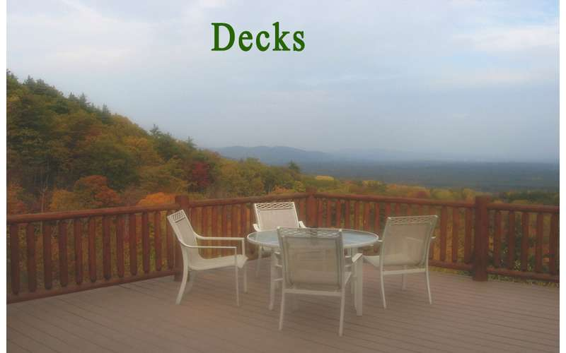 patio chairs and table on a deck overlooking a landscape