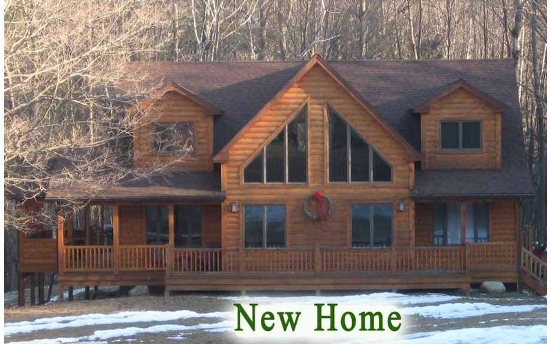 a large wooden lodge with two stories and a front deck