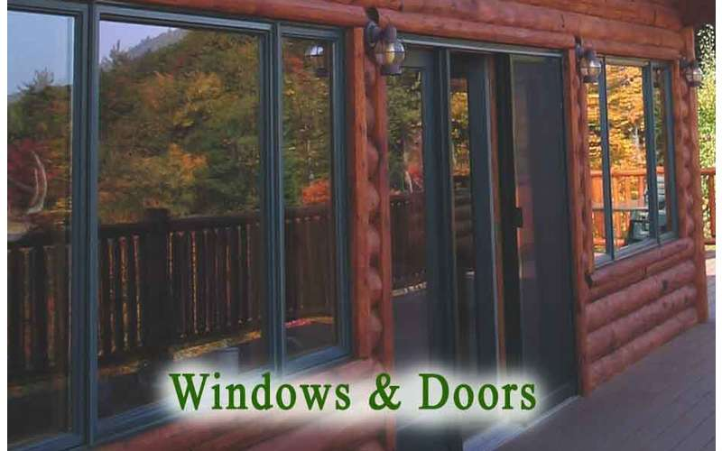 glass windows and doors on the front side of a brown wooden house