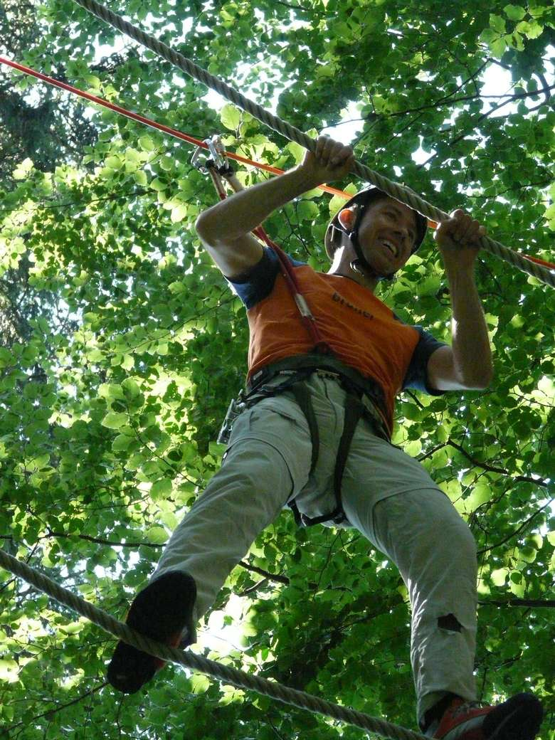 a man hanging between ropes on a treetop course