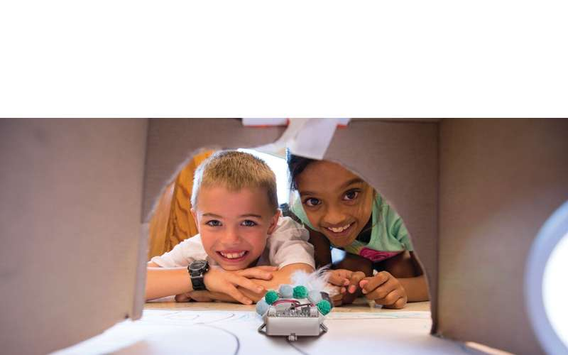 two kids looking at a small robot under an open box