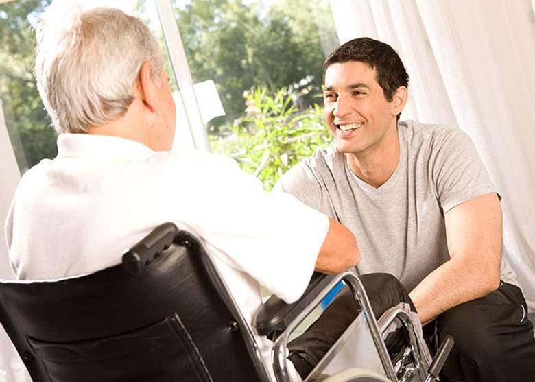 a man facing an elderly man in a wheelchair