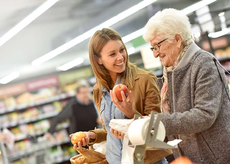 a woman helping an elderly woman with grocery shopping