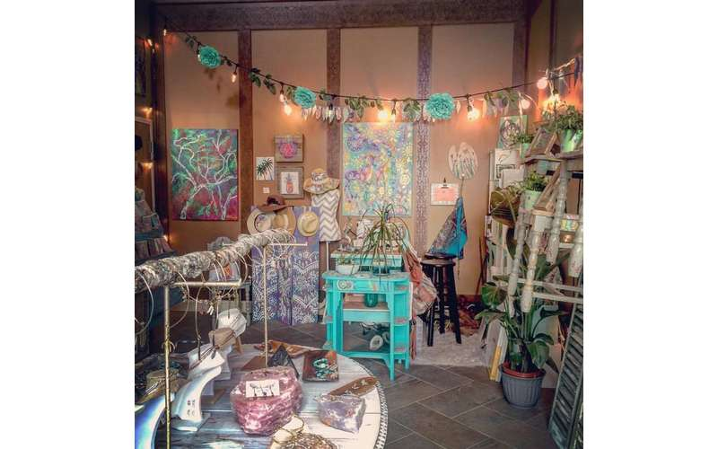an art studio with wall paintings, lights, jewelry, and more