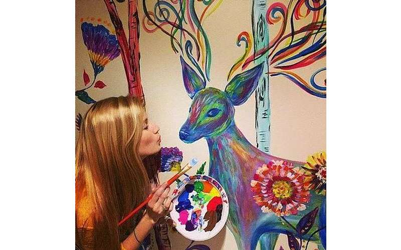 a woman painting a large and colorful deer