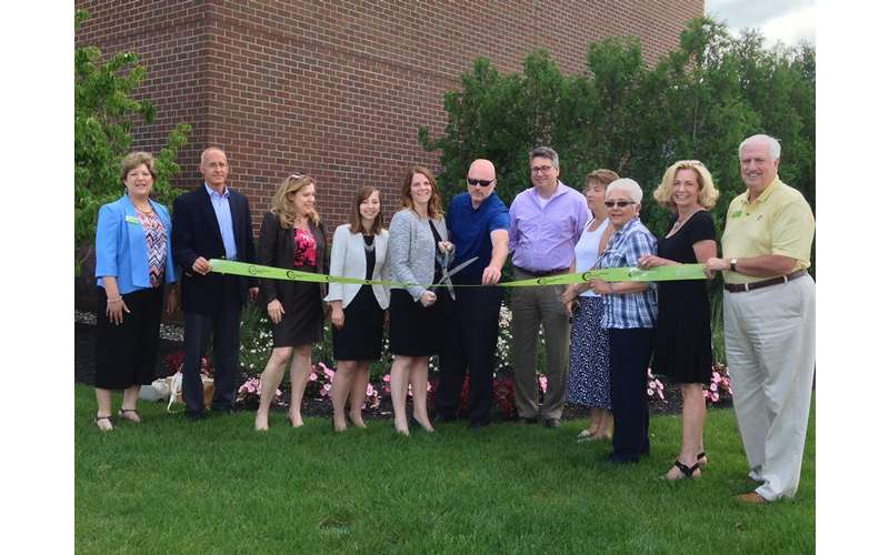 a group of people outdoors at a ribbon cutting