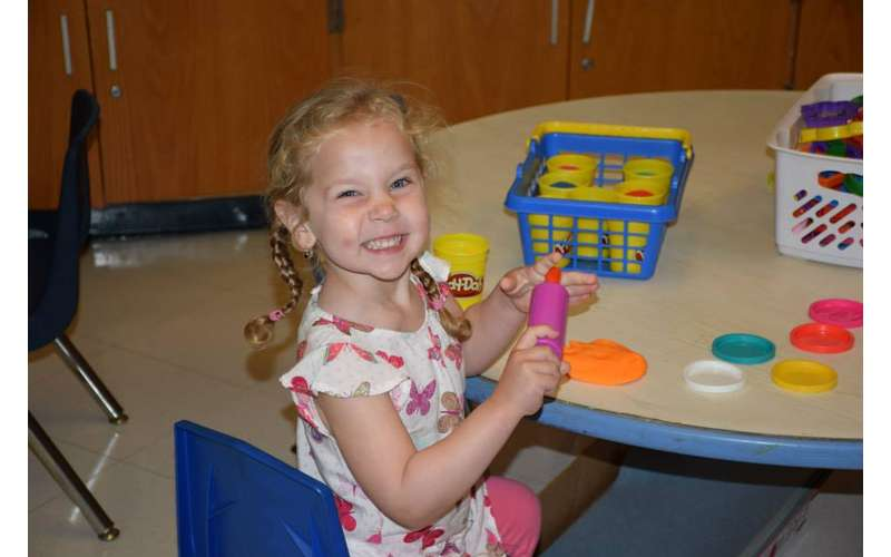 a little girl smiling and posing with play-doh