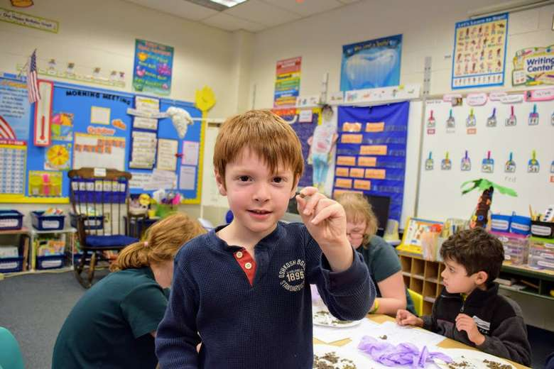 a little boy in a classroom holding up a pebble