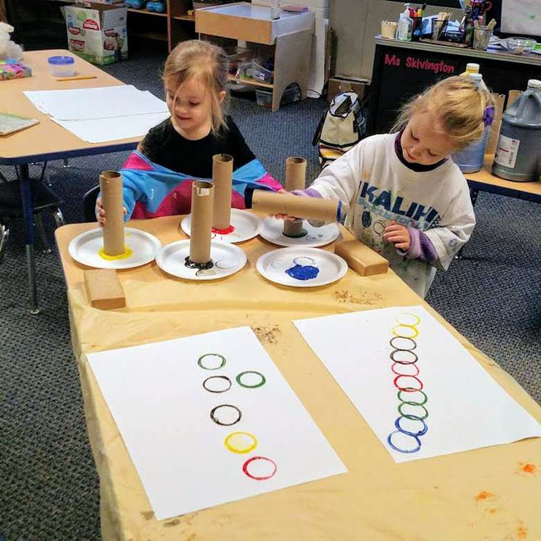 two young girls making art with paper towel rolls