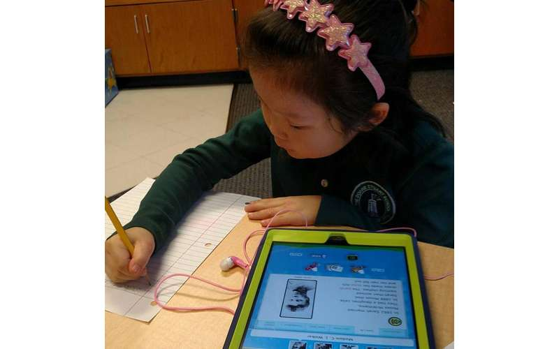 young girl writing something next to an ipad