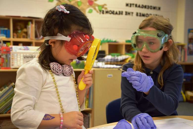 two girls working on a project with goggles on