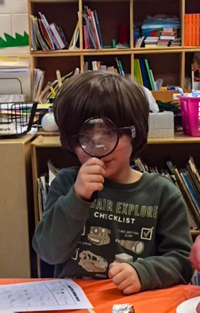 young boy with magnifying glass