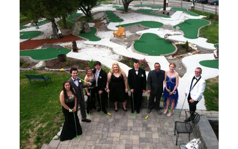 teens dressed for prom standing near a mini golf course