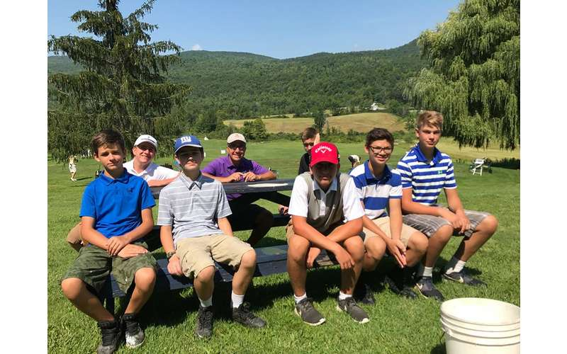 teens and adults at a picnic table at a golf course