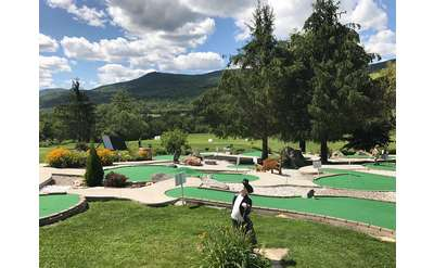 a mini golf course with a small statue nearby and trees and mountains in the background