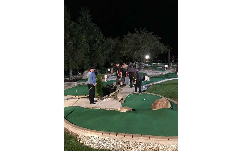 people playing on a mini golf course during the evening