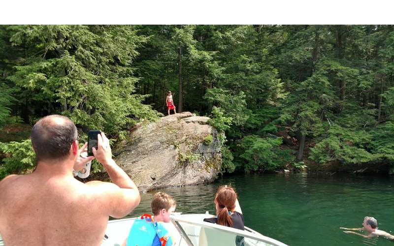 person in the background about to jump off a cliff, people in foreground, man taking picture