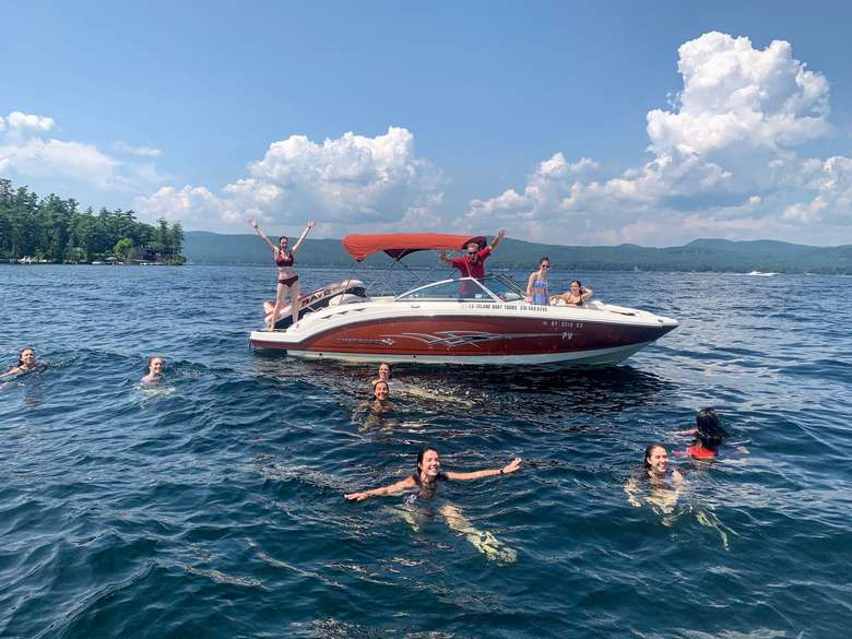 group of people swimming around a boat