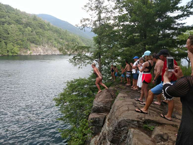 woman about to jump off a cliff into lake george while others look on