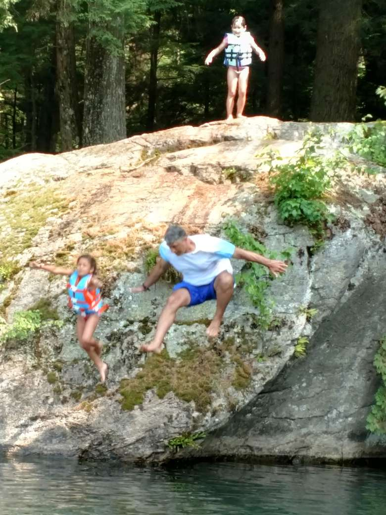 father and daughter jumping off a rock into lake george