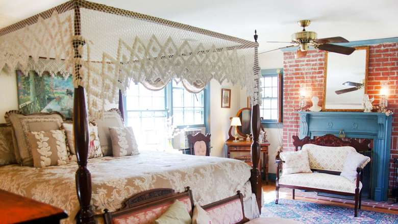a guest room with a big bed and a small chair nearby