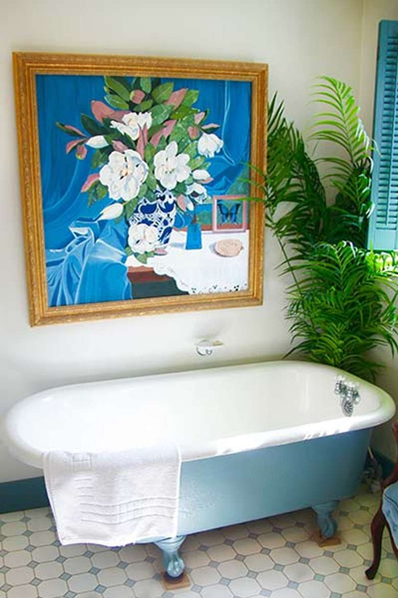 a white bathtub with a painting on the wall