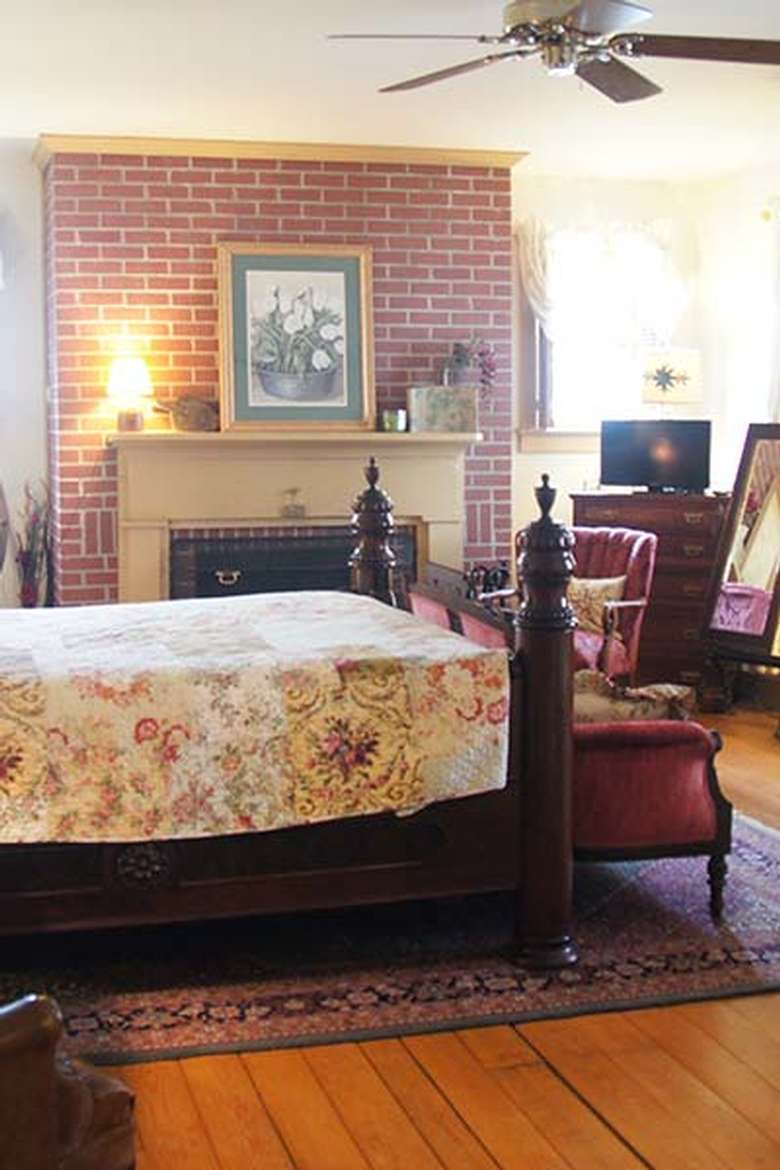 the end of a bed with a fireplace in the background