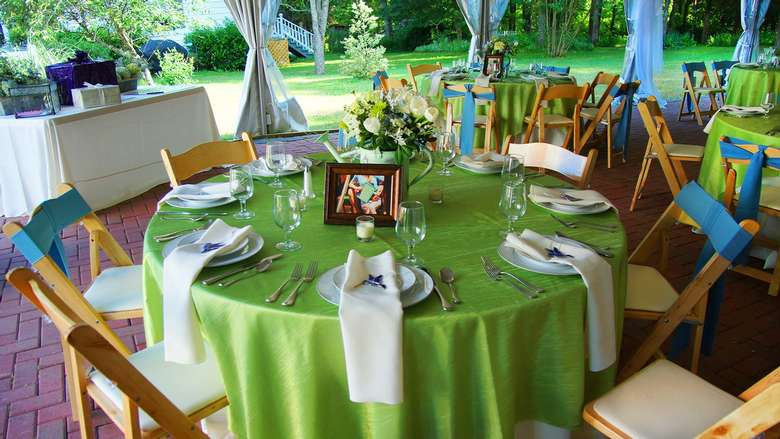 tables decorated with green tablecloth and plates