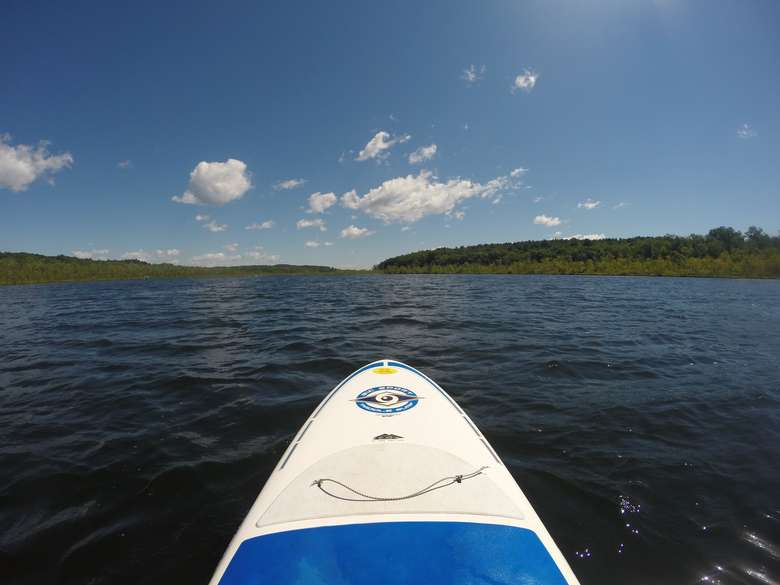 the front end of a stand up paddle board on the water