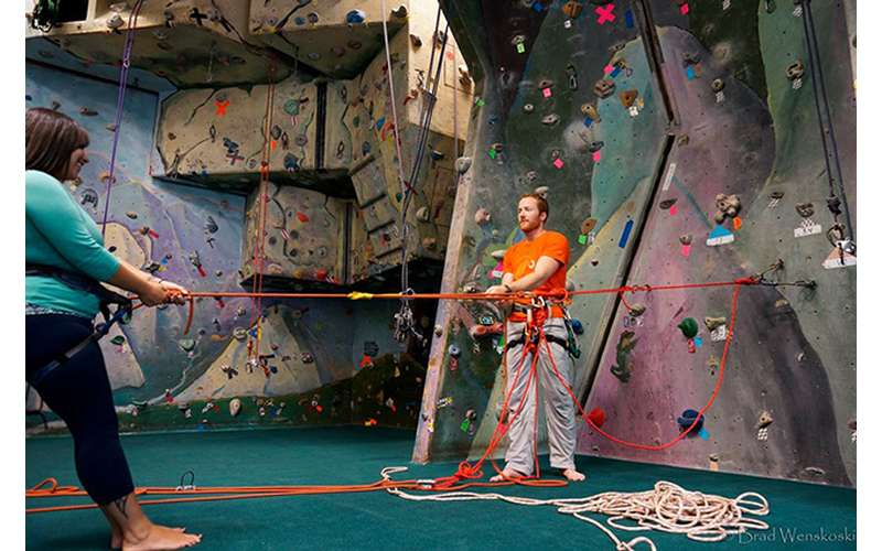 man and woman with ropes for indoor rock climbing