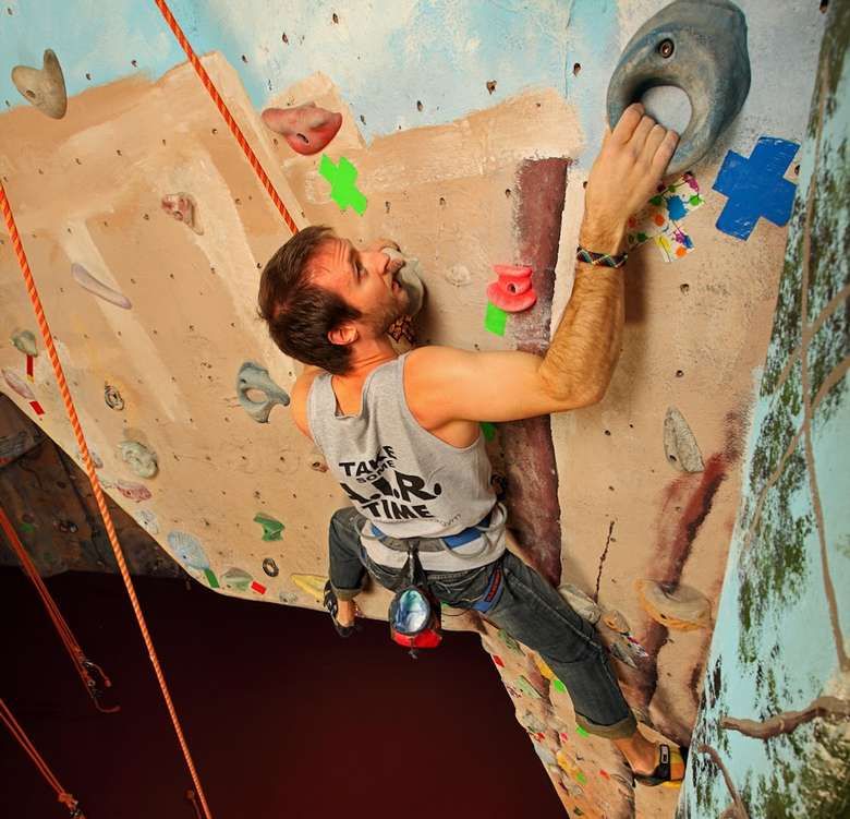 man reaching up on rock climbing wall