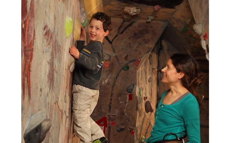 woman watching as boy enjoys rock climbing