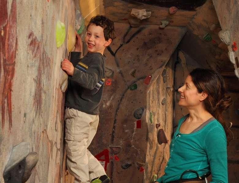 woman watching as boy enjoys rock climbing