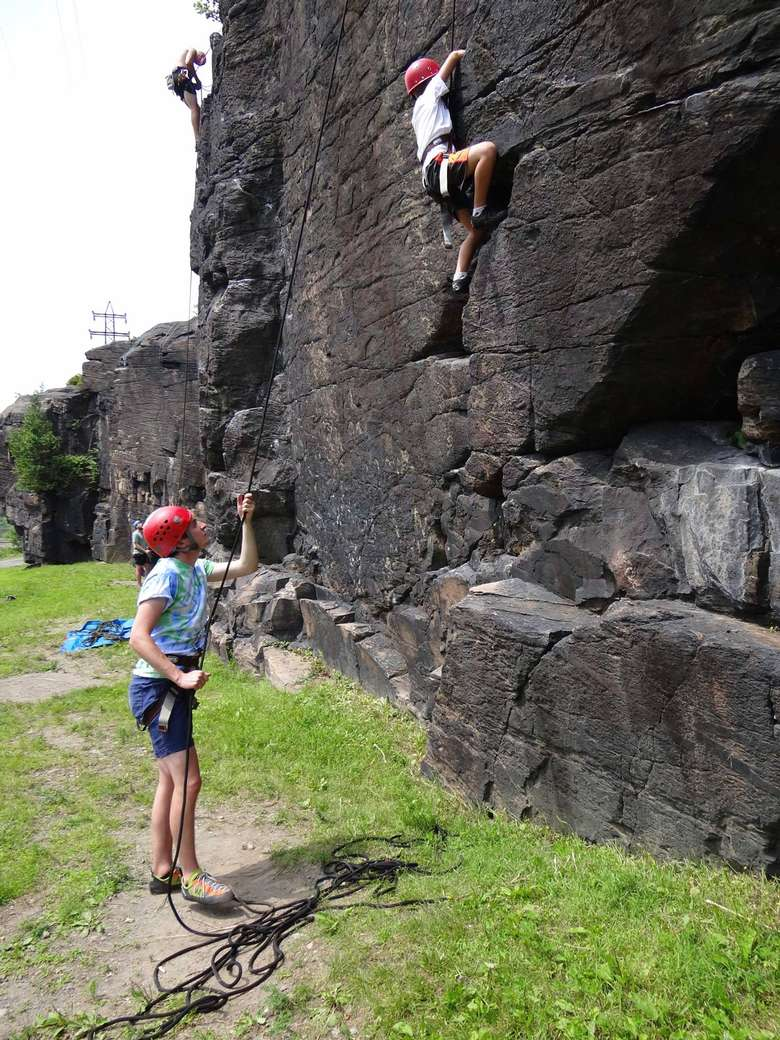 person climbing outdoors, person on the ground spotting