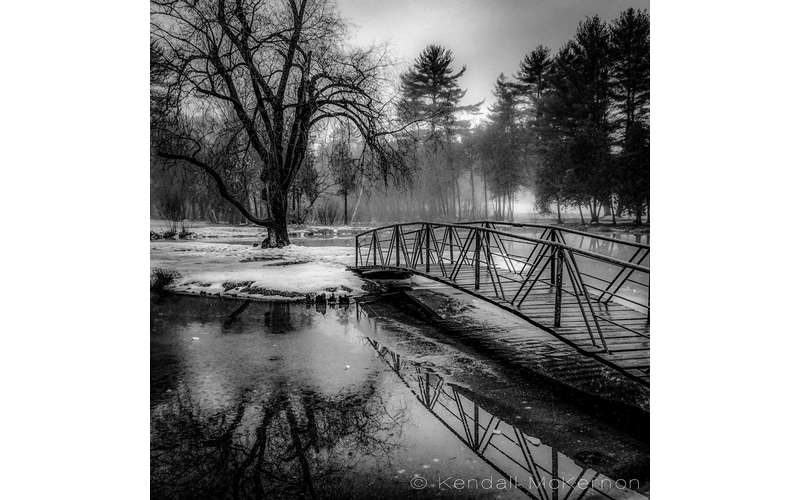 black and white photo of bridge over water