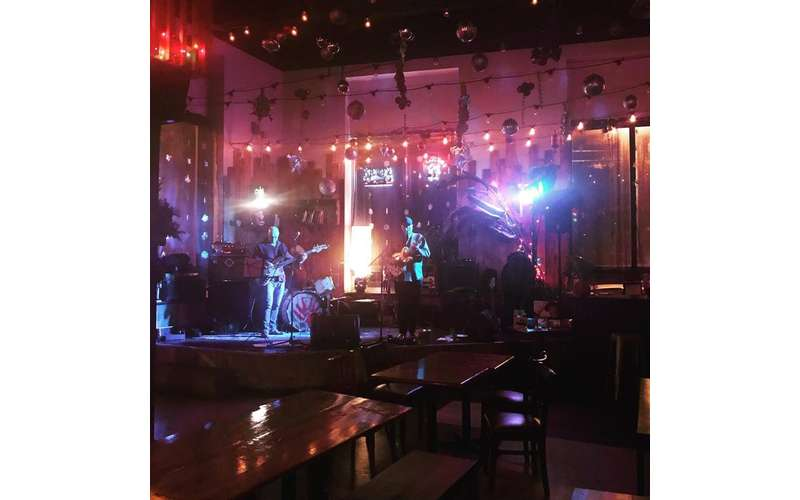 band performing on a small stage with colored lights shining